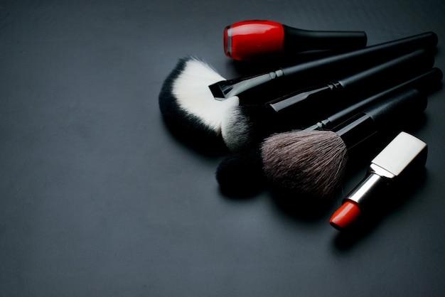 Divers produits de maquillage sur table sombre