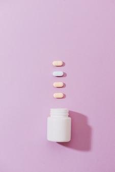 Divers produits pharmaceutiques. le tout sur fond rose.
