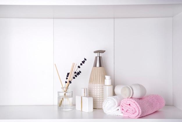 Divers produits de spa et de beauté sur une étagère blanche
