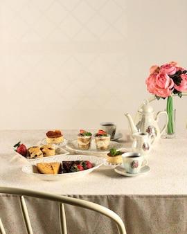 Divers réglages de gâteau en tranches pour la table de desserts à la fête, décorés de roses blanches et roses fraîches