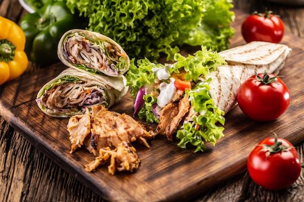 Divers repas de tortillas sur une planche à découper en bois.
