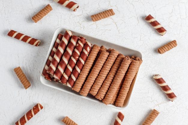 Divers rouleaux de gaufres dans des assiettes en céramique, vue du dessus.