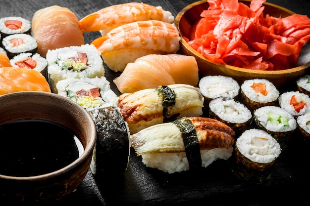 Divers rouleaux, sushis et makis sur une planche de pierre avec sauce soja et gingembre.