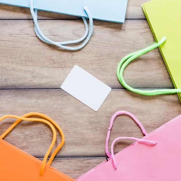 Divers sacs à provisions multicolores avec une carte blanche vierge sur un bureau en bois
