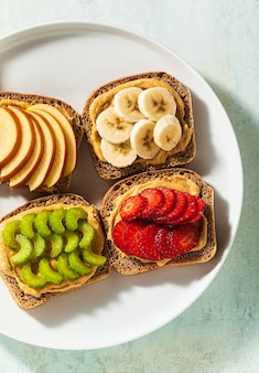 Divers sandwichs au beurre d'arachide et fraises, céleri, banane et pomme