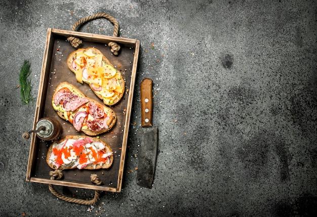 Divers sandwichs aux fruits de mer, viande et légumes sur l'ancien plateau sur table rustique.