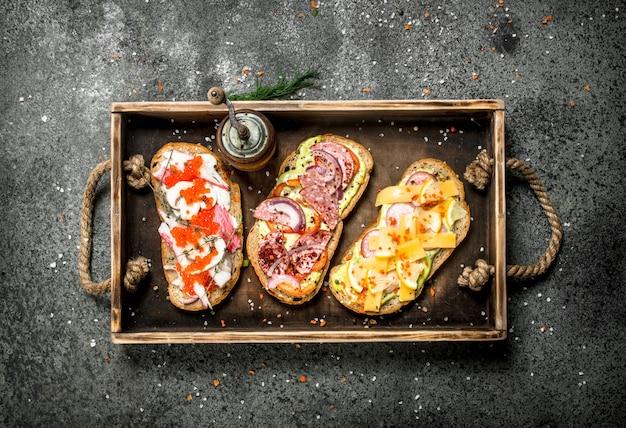 Divers sandwichs aux fruits de mer, viande et légumes sur un vieux plateau.