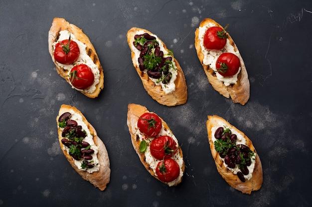 Divers sandwichs aux haricots rouges, tomates cerises au four, ail, huile d'olive et fromage blanc sur une surface sombre