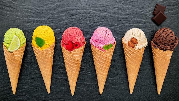 Divers de la saveur de la crème glacée dans les cônes mis en place sur fond de pierre sombre.
