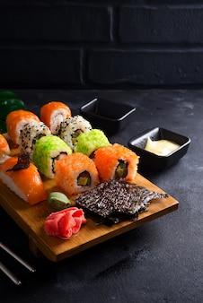 Divers sushis fixés sur une plaque en bois avec des bâtons d'ardoise, de la sauce et du nori sur fond noir