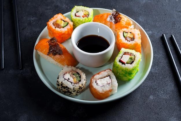 Divers sushis sur une plaque en céramique avec des bâtons d'ardoise, sauce sur fond noir
