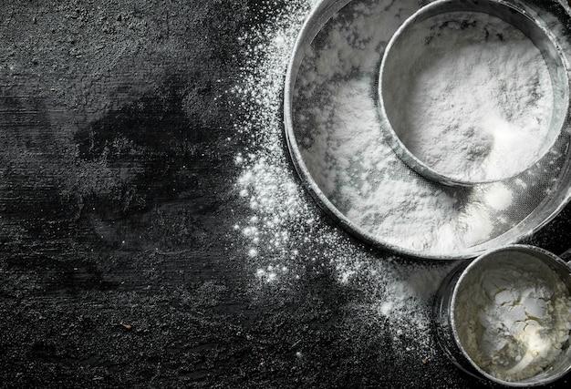 Divers tamis avec de la farine. sur une surface rustique noire
