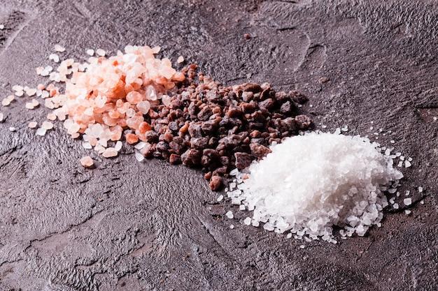 Divers tupes de sels, himalaya rose et noir avec du sel de mer sur fond d'ardoise