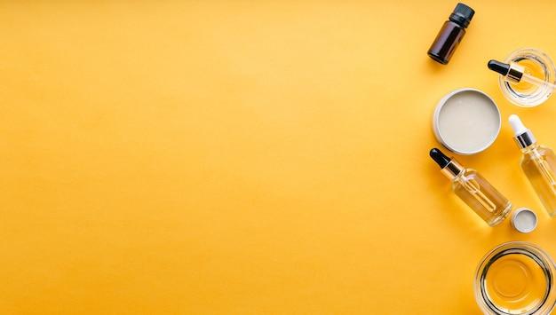 Divers types d'huiles cosmétiques dans des bocaux en verre et en métal, des flacons compte-gouttes, du beurre de sérum d'huile essentielle pour les soins de la peau et le traitement cosmétologique sur fond jaune avec espace de copie