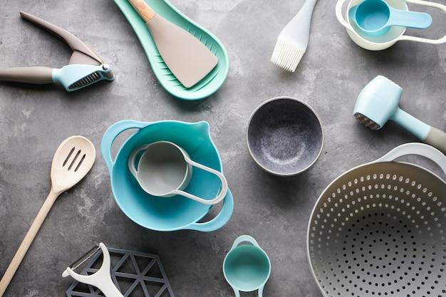 Divers ustensiles de cuisine sur table grise, pose à plat.