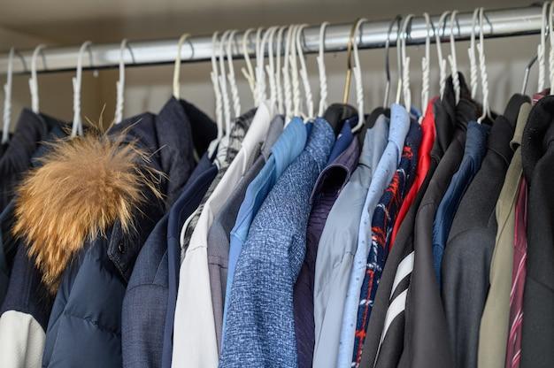Divers vêtements suspendus sur des cintres et remplissant le placard