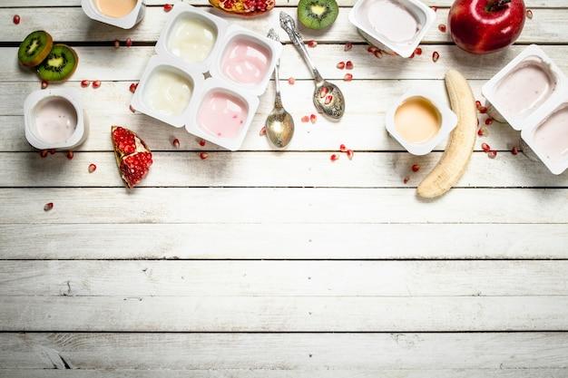 Divers yaourts aux fruits. sur une table en bois blanche.