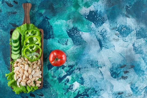 Diversement légumes et haricots sur une planche sur la table bleue.
