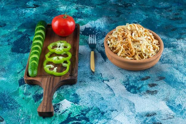 Diversement des légumes sur une planche à côté d'une fourchette et un bol de nouilles sur la table bleue.