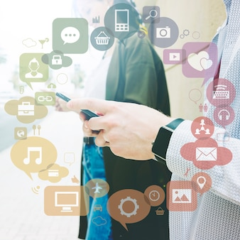 Diverses applications formant un cercle devant deux personnes utilisant un téléphone portable