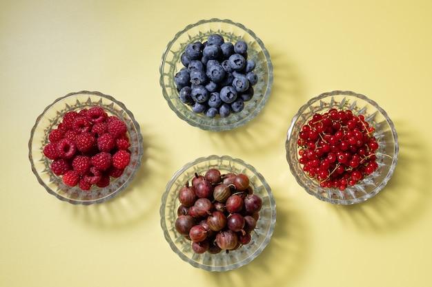 Diverses baies d'été dans des bols en verre sur fond jaune avec des aliments sains d'ombres