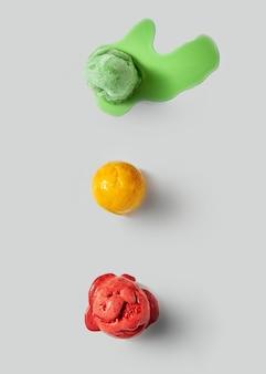 Diverses boules de délicieuse glace fondante avec des éclaboussures sur un fond de béton gris. copiez l'espace pour le texte. vue de dessus