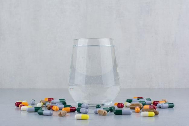 Diverses capsules pharmaceutiques et verre d'eau.