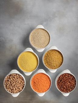 Diverses céréales brutes: couscous, haricots, quinoa, boulgour, lentilles, surface de béton gris pois chiches, vue de dessus,