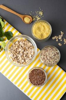Diverses céréales non cuites. différents types de gruaux dans des bols sur fond gris.
