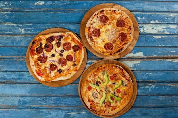 Diverses délicieuses pizzas italiennes servies sur un plateau à pizza