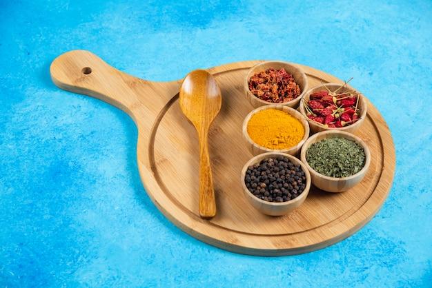 Diverses épices biologiques sur planche de bois.