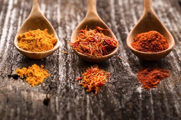 Diverses épices sur des cuillères en bois, ingrédients alimentaires