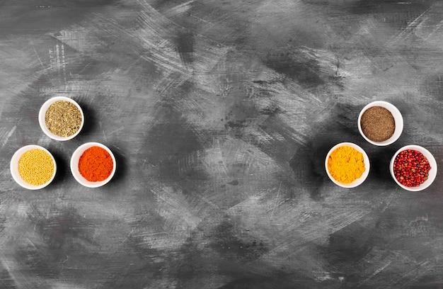 Diverses épices dans des bols blancs sur un espace sombre. vue de dessus, espace copie