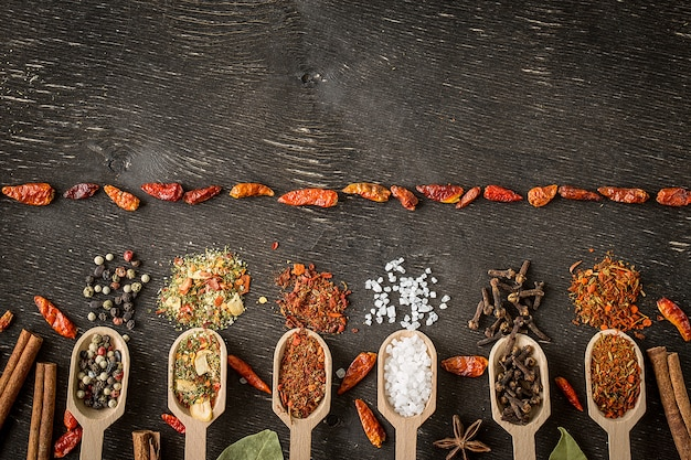 Diverses épices dans des cuillères en bois sur une table en bois foncée