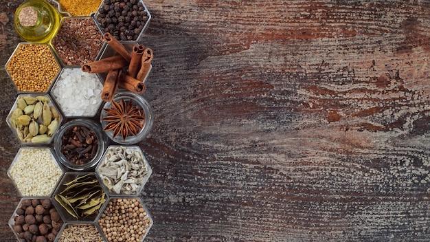 Diverses épices dans des pots hexagonaux sur une surface en bois