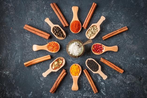 Diverses épices indiennes dans des cuillères en bois, des graines, des herbes sur une table en pierre sombre. épices colorées, vue de dessus. alimentation biologique, mode de vie sain, espace pour le texte