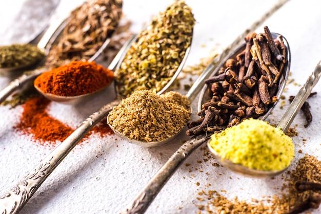 Diverses épices moulues curcuma poivre gingembre cannelle herbe assaisonnement paprika sel graines de carvi sur la table. vue d'en-haut. épices indiennes parfumées