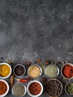 Diverses épices sèches à plat gisaient dans de petits bols sur fond gris. vue de dessus, espace de copie