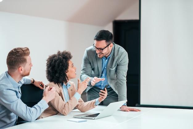 Diverses équipes commerciales du millénaire travaillant ensemble dans une salle de réunion.