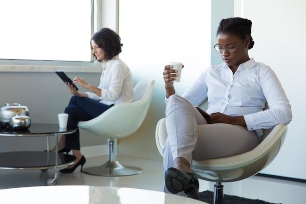 Diverses femmes d'affaires avec des gadgets buvant du café
