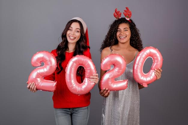 Diverses femmes avec des ballons de nouvel an 2020 portant un chapeau de noël isolé sur gris