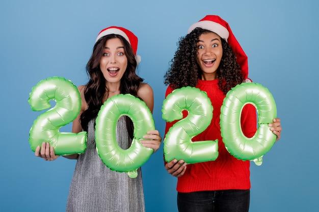 Diverses femmes avec des ballons de nouvel an 2020 portant des chapeaux de noël isolés