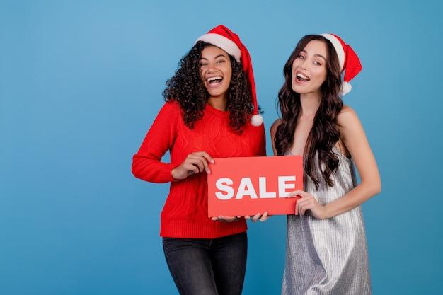 Diverses femmes portant des chapeaux de santa avec signe de vente rouge