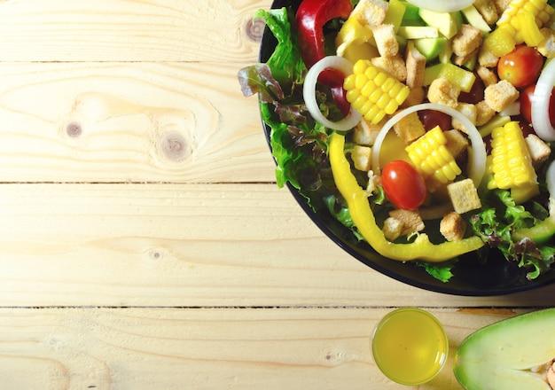 Diverses feuilles de salade fraîche à la tomate dans un bol sur fond en bois