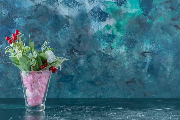 Diverses fleurs dans un verre , sur fond bleu.