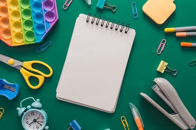Diverses fournitures scolaires colorées et un réveil sur fond de papier vert. concept d'éducation. mise à plat, vue de dessus, espace de copie mock up