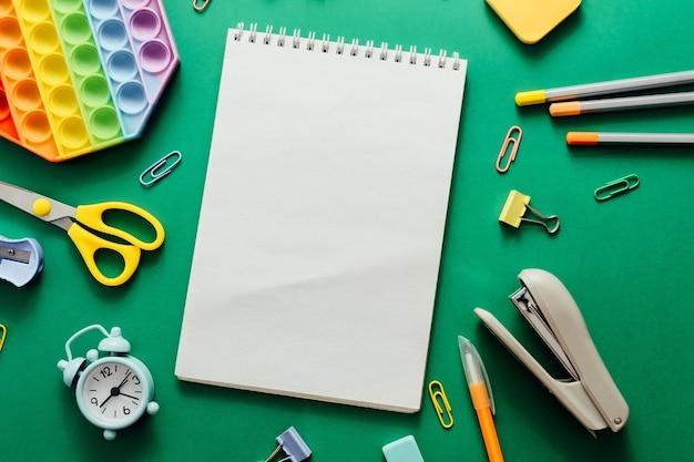 Diverses fournitures scolaires colorées et un réveil sur fond de papier vert. retour au concept d'école et d'éducation. mise à plat, vue de dessus, espace de copie mock up