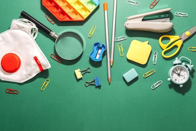 Diverses fournitures scolaires sur fond vert minable en forme de commission scolaire bienvenue à l'école...