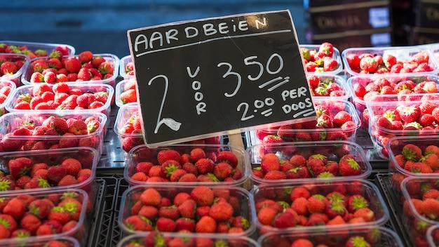 Diverses fraises avec prix affiché sur un marché de producteurs locaux