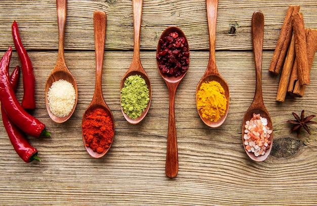 Diverses herbes et épices colorées sur table en bois